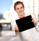 Portrait of young man showing digital tablet against a building — Stock fotografie