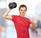 Young man doing fitness with weights indoor — Stock Photo