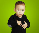 Portrait of adorable kid touching his stomach against a green ba — Stock Photo