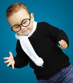 Portrait of kid wearing glasses looking down against a blue back — Stock Photo