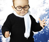 Portrait of kid wearing glasses looking down agaisnt a blue clou — Stock Photo
