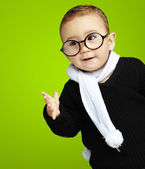 Portrait of adorable kid gesturing doubt against a green backgro — Stock Photo