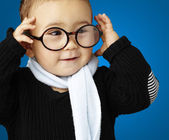 Portrait of funny kid holding his glasses against a blue backgr — Stock Photo