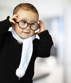 Portrait of funny kid holding his glasses indoor — Stock Photo