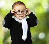 Portret van grappige jongen zijn bril houden tegen een natuur-rug — Stockfoto