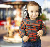 Portrait of a handsome kid listening to music and smiling agains — Stock Photo