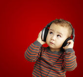 Portrait of a handsome kid listening to music looking up over re — Stockfoto