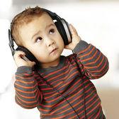 Ritratto di un ragazzo bello, ascoltando musica, guardando in alto indoor — Foto Stock