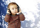Ritratto di un bambino bello ascoltare musica alla ricerca contro — Foto Stock