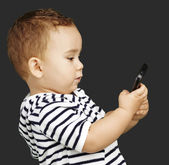 Portrait of funny kid touching mobile over black background — Stock Photo