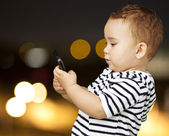 Portrait of funny kid touching mobile at city by night — ストック写真