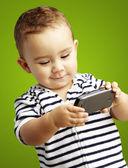 Retrato de niño divertido jugando con móvil sobre fondo verde — Foto de Stock