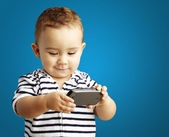Portrait of funny kid playing with mobile over blue background — Stockfoto