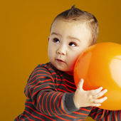 Portrait de drôle enfant tenant un gros ballon orange sur orange b — Photo