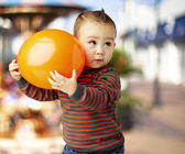 Portret van grappige jongen met een grote oranje ballon tegen een auto — Stockfoto