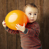 Portrait of funny kid holding a big orange balloon against a woo — ストック写真