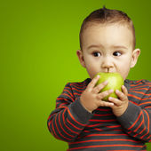 Portrait of a handsome kid bitting a green apple over green back — Stock Photo