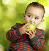 Portrait of a handsome kid bitting a green apple at park — Stock Photo