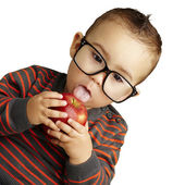Portrait of a handsome kid wearing glasses sucking a red apple o — Stock Photo
