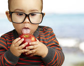 Portrait of a handsome kid wearing glasses sucking a red apple n — Stock Photo