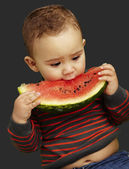 Portrait of a handsome kid holding a watermelon and sucking over — Stockfoto