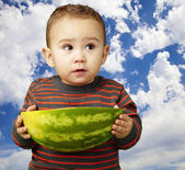 Portrait of sweet kid holding a big watermelon against a cloudy — Stockfoto