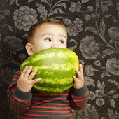 Portrait of a handsome kid holding watermelon and sucking agains — Foto de Stock
