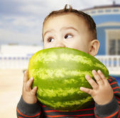 Portrait of a handsome kid holding watermelon and sucking at hou — ストック写真