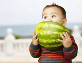 Portrait of a handsome kid holding watermelon and sucking near t — Стоковое фото