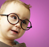 Portrait of sweet kid wearing round glasses over pink background — Stock Photo
