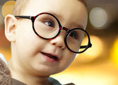 Portrait of kid wearing round glasses against a abstract backgro — Stock fotografie