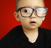 Portrait of kid wearing glasses over red background — Stok fotoğraf