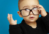 Portrait of serious kid wearing glasses and doing a gesture over — Stock Photo