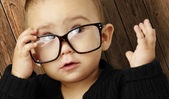 Portrait of kid wearing glasses and looking up against a wooden — Stock Photo