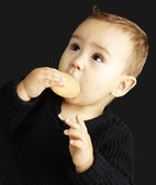 Portrait of kid eating a biscuit over black background — Stockfoto