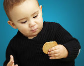 Portrait of handsome kid eating a biscuit against a blue backgro — Stockfoto