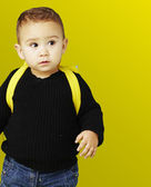 Portrait of adorable kid carrying yellow backpack over yellow ba — Stock Photo