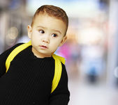 Portrait of adorable kid carrying yellow backpack at a crowded p — ストック写真