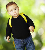 Portrait of adorable kid carrying yellow backpack against a natu — Stockfoto