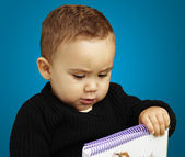 Portrait of kid holding notebook over blue background — Stock Photo