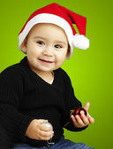 Portrait of happy kid wearing a christmas bonnet over green back — Stock Photo