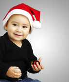 Portrait of happy kid wearing a christmas bonnet over grey backg — Stock Photo
