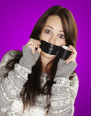 Portrait of scared girl being silenced by herself over purple ba — Stockfoto