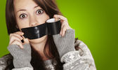 Portrait of scared girl being silenced by herself over green bac — Stockfoto