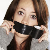 Portrait of scared girl being silenced by herself against a abst — ストック写真