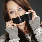 Portrait of scared girl being silenced by herself over black bac — ストック写真