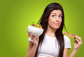 Portrait of young woman choosing pizza or salad against a green — Stockfoto