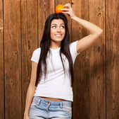 Portrait of young woman holding orange on her head against a woo — Stok fotoğraf