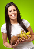 Portrait of young woman holding tropical fruits against a green — Stock Photo