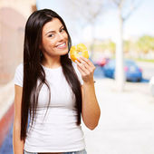 Portrait of young woman eating a donut at city — Stock Photo